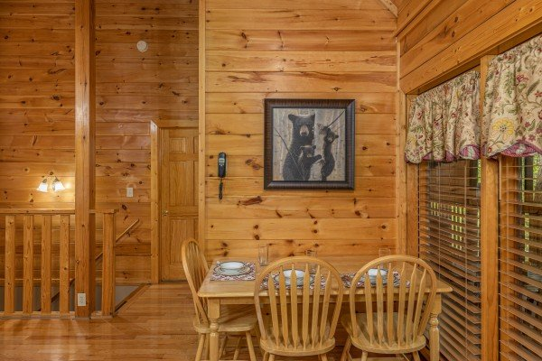 Dining table and chairs for three at Location Location Location, a 1 bedroom cabin rental located in Pigeon Forge