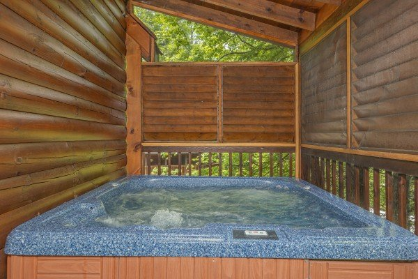 Hot tub and privacy fence on a covered deck at Location Location Location, a 1 bedroom cabin rental located in Pigeon Forge