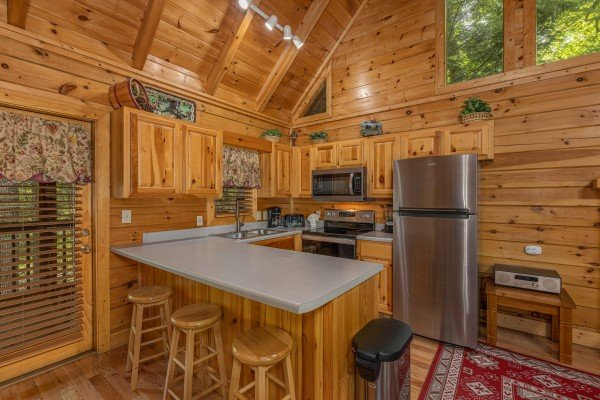 Kitchen with breakfast bar for three at Location Location Location, a 1 bedroom cabin rental located in Pigeon Forge