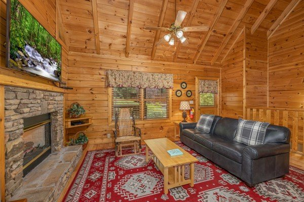 Fireplace, TV, and seating in a living room at Location Location Location, a 1 bedroom cabin rental located in Pigeon Forge