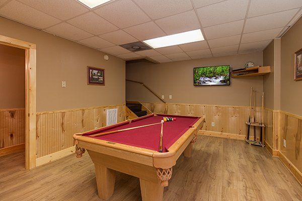 Red felt pool table in the game room at Location Location Location, a 1 bedroom cabin rental located in Pigeon Forge