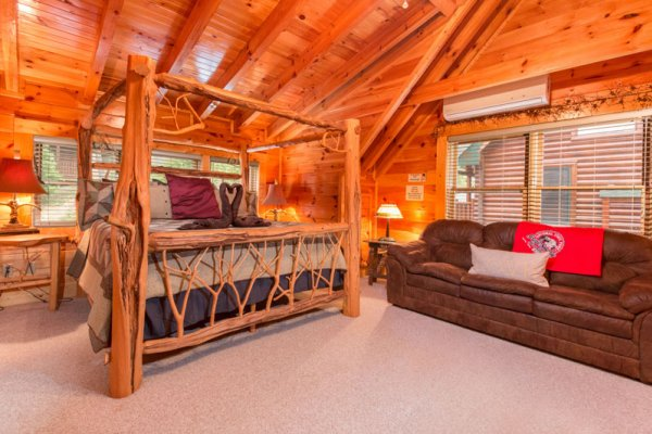 King-sized custom log canopy bed and a sofa bed at Bearfoot Lodge, a 5-bedroom cabin rental located in Pigeon Forge