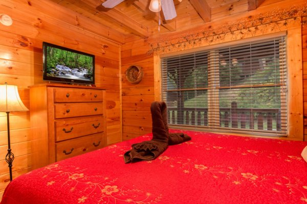 Bedroom with television and dresser at Bearfoot Lodge, a 5-bedroom cabin rental located in Pigeon Forge