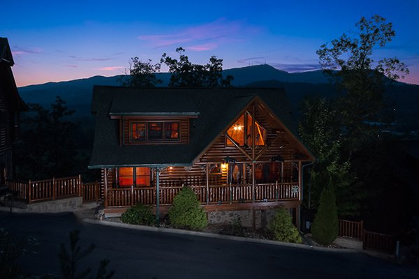 A cabin lit up at night with the sunset at Bearfoot Lodge, a 5-bedroom cabin rental located in Pigeon Forge