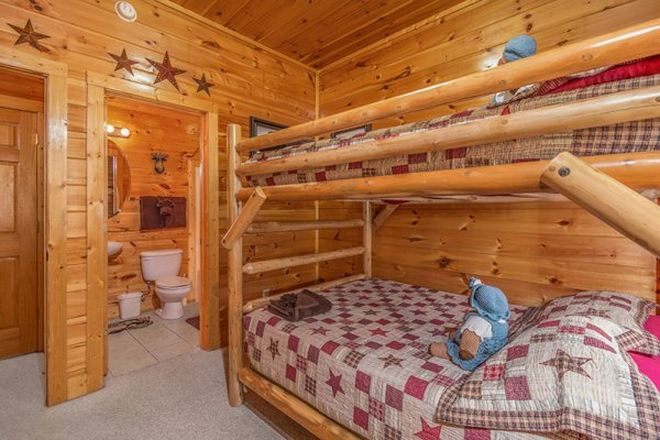 Bunk bed room with attached bath at Bearfoot Lodge, a 5-bedroom cabin rental located in Pigeon Forge