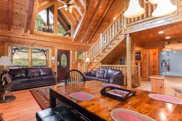 Living room and dining room open concept at Bearfoot Lodge, a 5-bedroom cabin rental located in Pigeon Forge