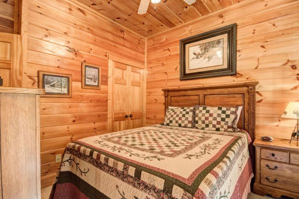 Bedroom with a wooden bed at Bearfoot Lodge, a 5-bedroom cabin rental located in Pigeon Forge