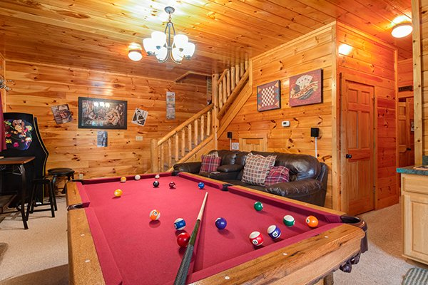 Game room with red felted pool table at Bearfoot Lodge, a 5-bedroom cabin rental located in Pigeon Forge