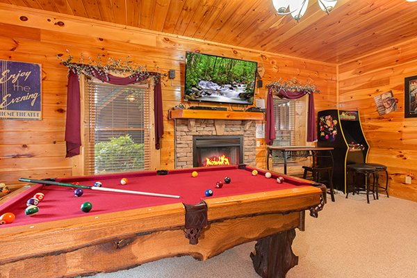 Game room with a fireplace and television at Bearfoot Lodge, a 5-bedroom cabin rental located in Pigeon Forge