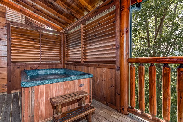 Hot tub on a covered porch with privacy fence at Bearfoot Lodge, a 5-bedroom cabin rental located in Pigeon Forge