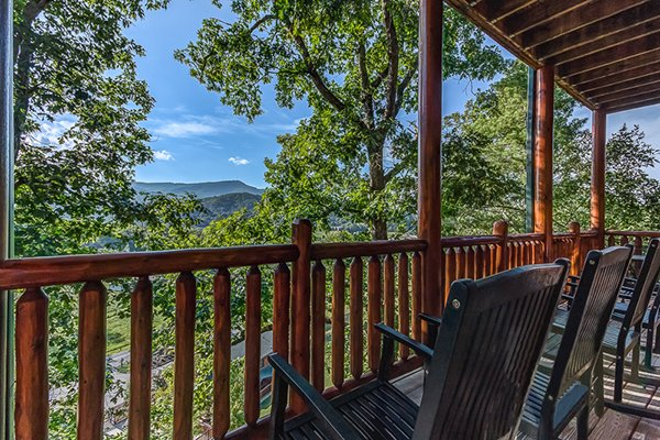 Rocking chairs on the covered porch looking at the mountain views at Bearfoot Lodge, a 5-bedroom cabin rental located in Pigeon Forge