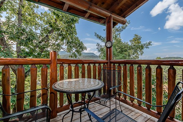 Bistro table on a covered deck with mountain views at Bearfoot Lodge, a 5-bedroom cabin rental located in Pigeon Forge