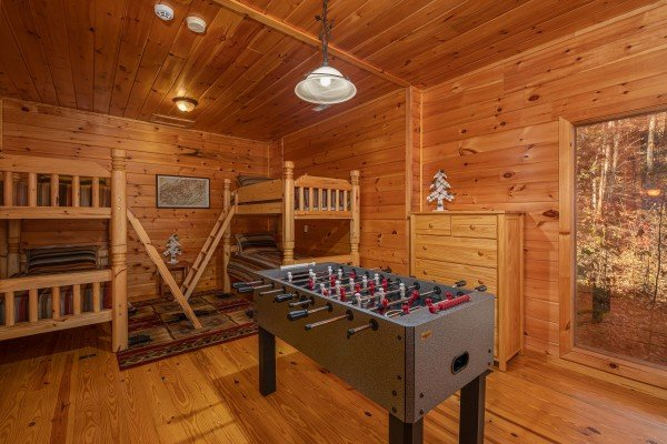 Foosball table and bunk beds in a room at All Hours, a 2 bedroom cabin rental located in Pigeon Forge
