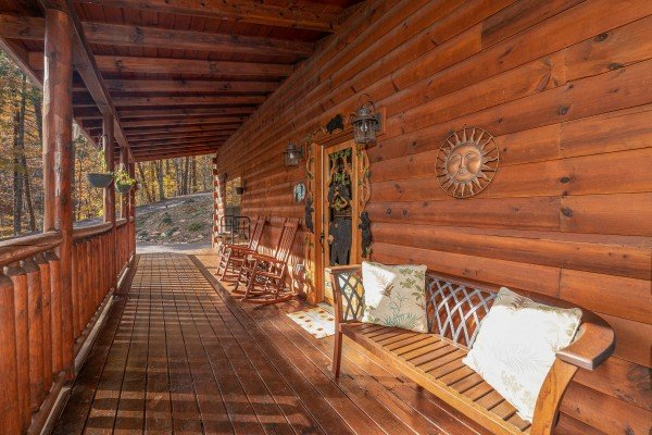 Front porch with bench, rocking chairs, and custom woodwork at All Hours, a 2 bedroom cabin rental located in Pigeon Forge
