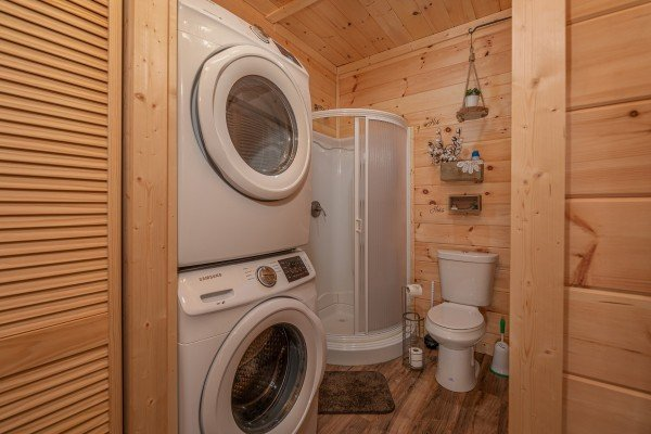 Half bath with a small shower and laundry room at All Hours, a 2 bedroom cabin rental located in Pigeon Forge