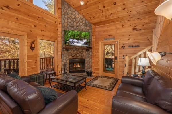 Fireplace and TV in the living room at All Hours, a 2 bedroom cabin rental located in Pigeon Forge