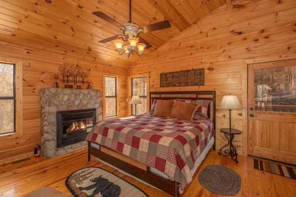 Bedroom with a fireplace at All Hours, a 2 bedroom cabin rental located in Pigeon Forge