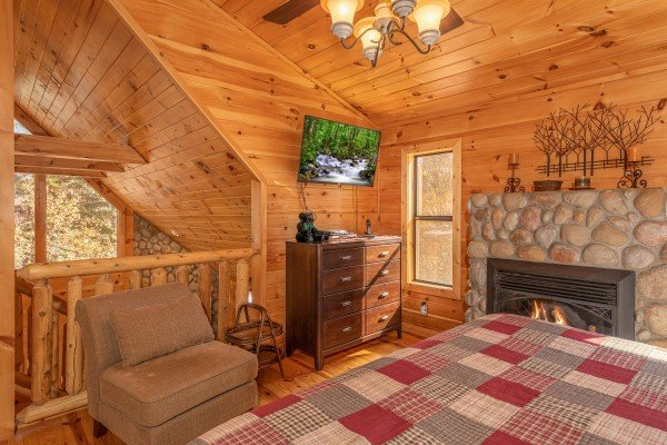 Dresser, TV, chair, and fireplace in a bedroom at All Hours, a 2 bedroom cabin rental located in Pigeon Forge