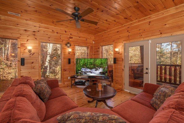 Lower level living room with sectional sofa, TV, and deck access at All Hours, a 2 bedroom cabin rental located in Pigeon Forge