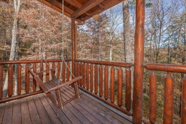 Porch swing on a covered deck at All Hours, a 2 bedroom cabin rental located in Pigeon Forge