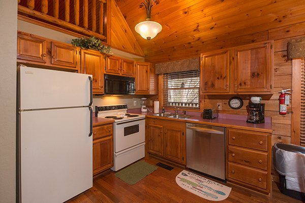 A kitchen with all major appliances and a kitchen window over the sink at Golden Memories, a 1-bedroom cabin rental located in Pigeon Forge