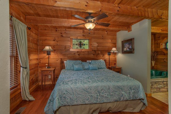 King-sized bed on the main floor at Golden Memories, a 1-bedroom cabin rental located in Pigeon Forge