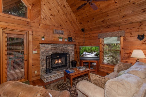 Living room with a stone fireplace and large television at Golden Memories, a 1-bedroom cabin rental located in Pigeon Forge