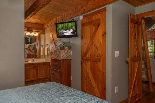 Bedroom with an en suite bath and wall-mounted television at Golden Memories, a 1-bedroom cabin rental located in Pigeon Forge