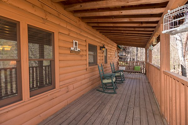 Covered deck with rocking chairs and a swing at Golden Memories, a 1-bedroom cabin rental located in Pigeon Forge