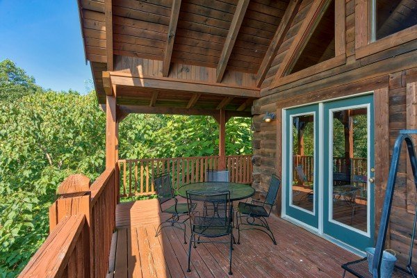 dining space for four on a covered deck at angel's majestic view a 3 bedroom cabin rental located in pigeon forge
