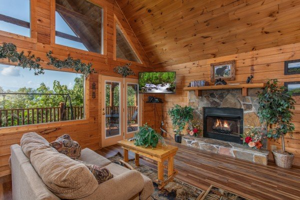 stone fireplace and wall mounted television at angel's majestic view a 3 bedroom cabin rental located in pigeon forge