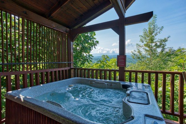 hot tub on a covered deck at angel's majestic view a 3 bedroom cabin rental located in pigeon forge