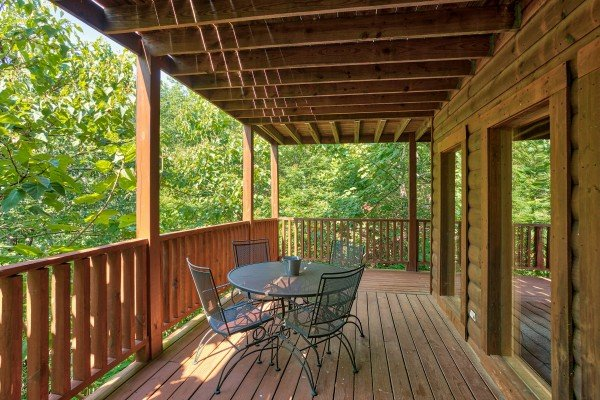 outdoor dining with space for four on a covered deck at angel's majestic view a 3 bedroom cabin rental located in pigeon forge