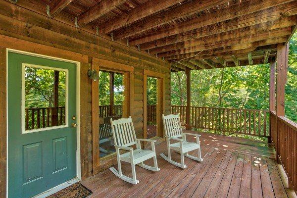 rocking chairs on a covered deck at angel's majestic view a 3 bedroom cabin rental located in pigeon forge