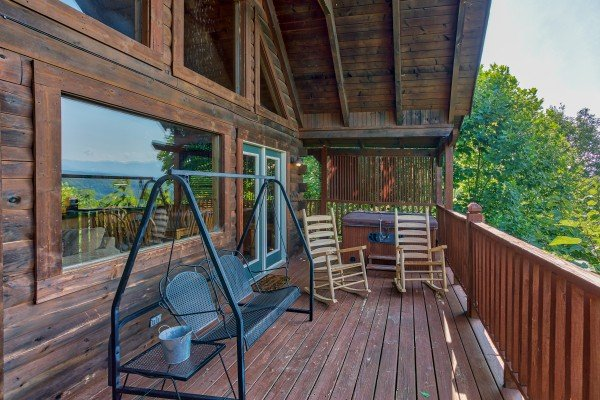 porch swing on a covered deck at angel's majestic view a 3 bedroom cabin rental located in pigeon forge