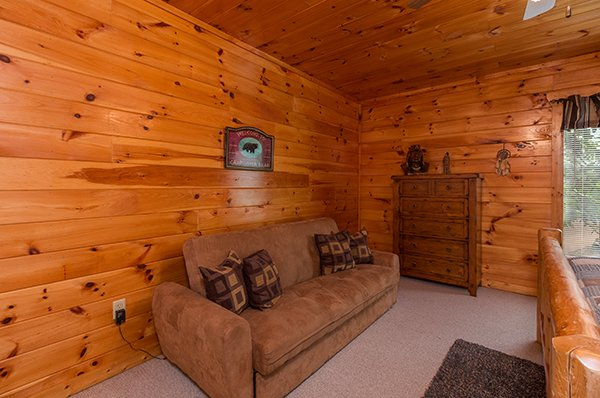 Couch and dresser in a bedroom at A Beautiful Memory, a 4 bedroom cabin rental located in Pigeon Forge