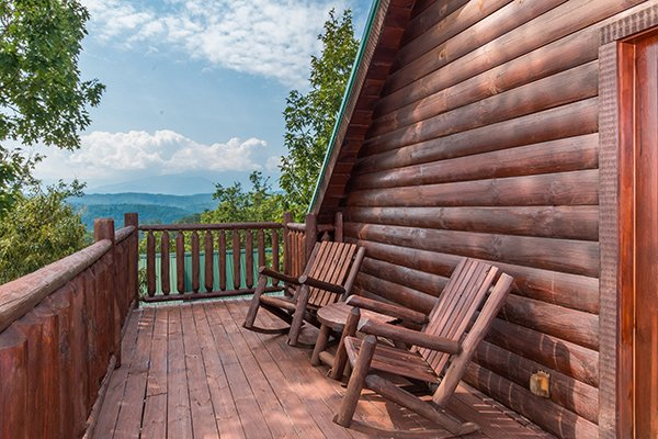 rocking chairs on a deck with a view at a beautiful memory a 4 bedroom cabin rental located in pigeon forge