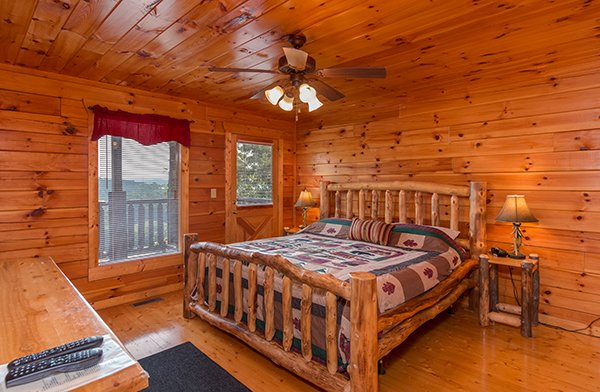 A king sized log bed at A Beautiful Memory, a 4 bedroom cabin rental located in Pigeon Forge