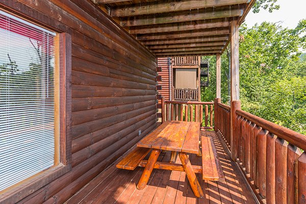 Picnic table on a covered deck at A Beautiful Memory, a 4 bedroom cabin rental located in Pigeon Forge
