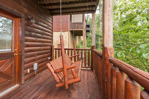 porch swing on the deck at a beautiful memory a 4 bedroom cabin rental located in pigeon forge