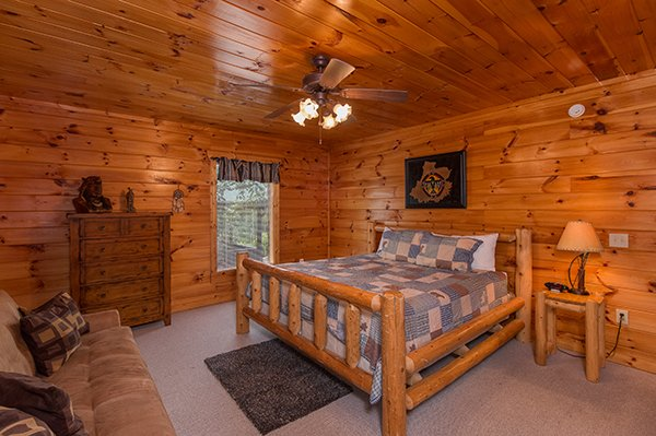 log bed with dresser and couch at a beautiful memory a 4 bedroom cabin rental located in pigeon forge