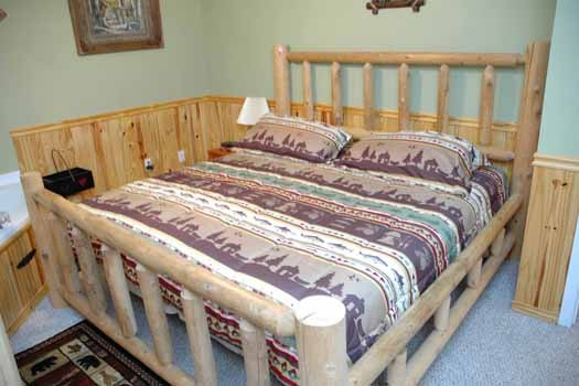king sized bed in a bedroom at i love view a 2 bedroom cabin rental located in pigeon forge