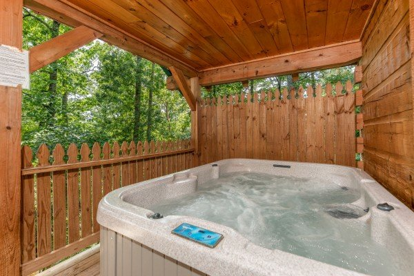 Hot tub with privacy fence on a covered deck at Just Us, a 1 bedroom cabin rental located in Pigeon Forge