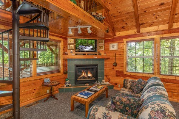 Fireplace, TV, sofa, and spiral staircase in the living room at Just Us, a 1 bedroom cabin rental located in Pigeon Forge