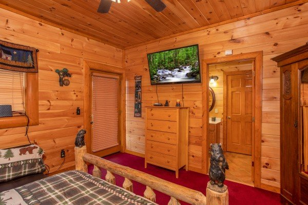 Bedroom with dresser television and attached bath at Pool'n Around in the Smokies, a 4 bedroom cabin rental located in Sevierville