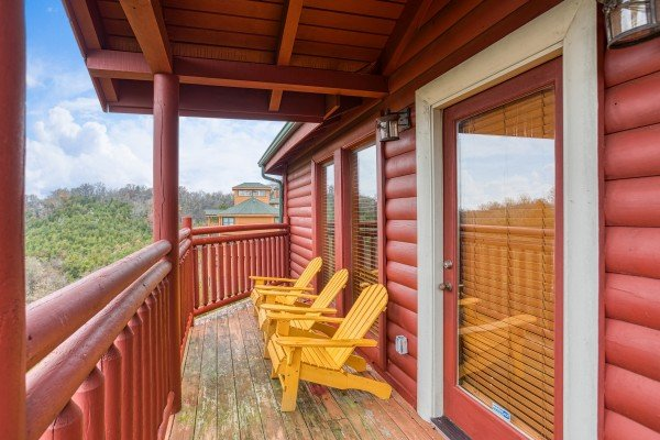 Three yellow adirondack chairs on a covered deck at Pool'n Around in the Smokies, a 4 bedroom cabin rental located in Sevierville