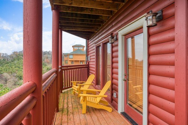 Yellow adirondack chairs on a covered porch at Pool'n Around in the Smokies, a 4 bedroom cabin rental located in Sevierville