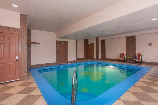 Indoor pool with shamrock inlay and deck chairs at Pool'n Around in the Smokies, a 4 bedroom cabin rental located in Sevierville