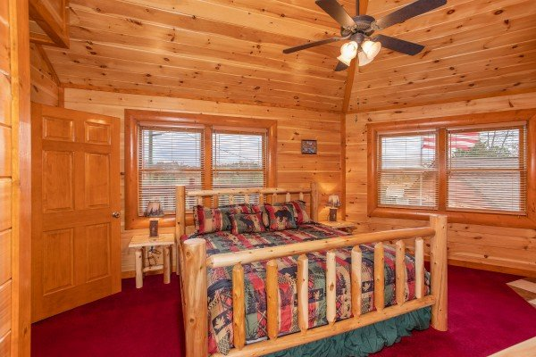 King sized log bed with vaulted ceiling at Pool'n Around in the Smokies, a 4 bedroom cabin rental located in Sevierville