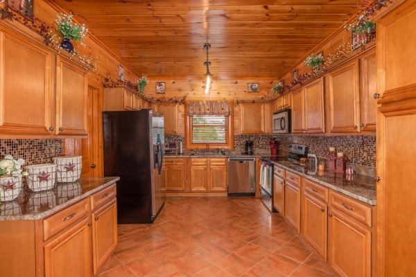 Large galley kitchen with stainless steel appliances at Pool'n Around in the Smokies, a 4 bedroom cabin rental located in Sevierville